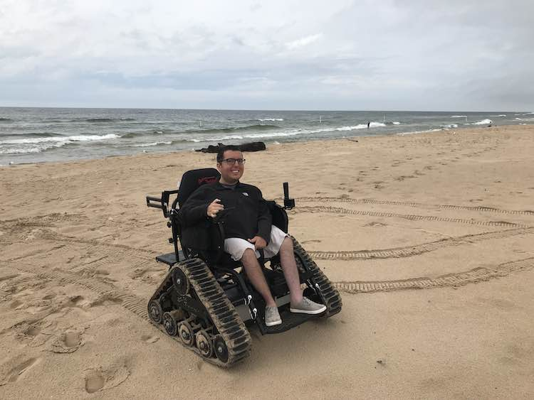 Cory Lee on beach in wheelchair